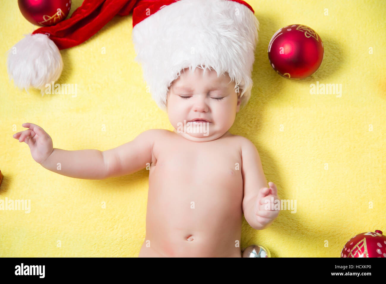 crying baby in a red Santa hat with balls on the New year tree. Beautiful little baby celebrates Christmas Stock Photo