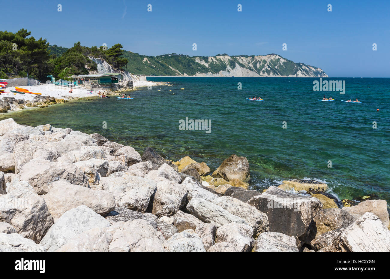Canoe in the bay surrounded by the turquoise sea, Province of Ancona, Conero Riviera, Marche, Italy - Stock Image