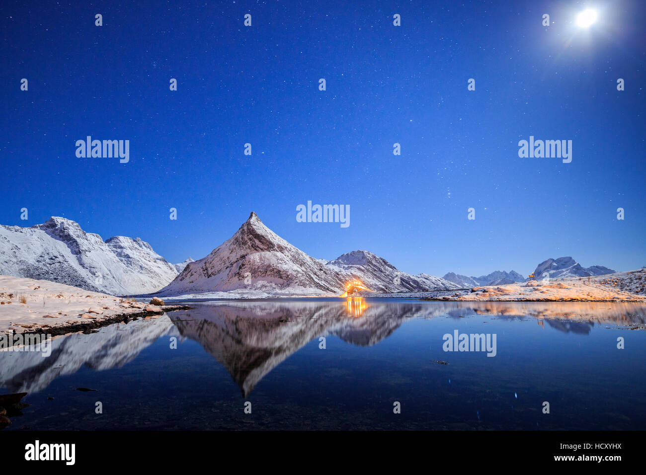Full moon and stars light up the snow capped peaks reflected in sea, Volanstinden, Fredvang, Lofoten Islands, Northern - Stock Image