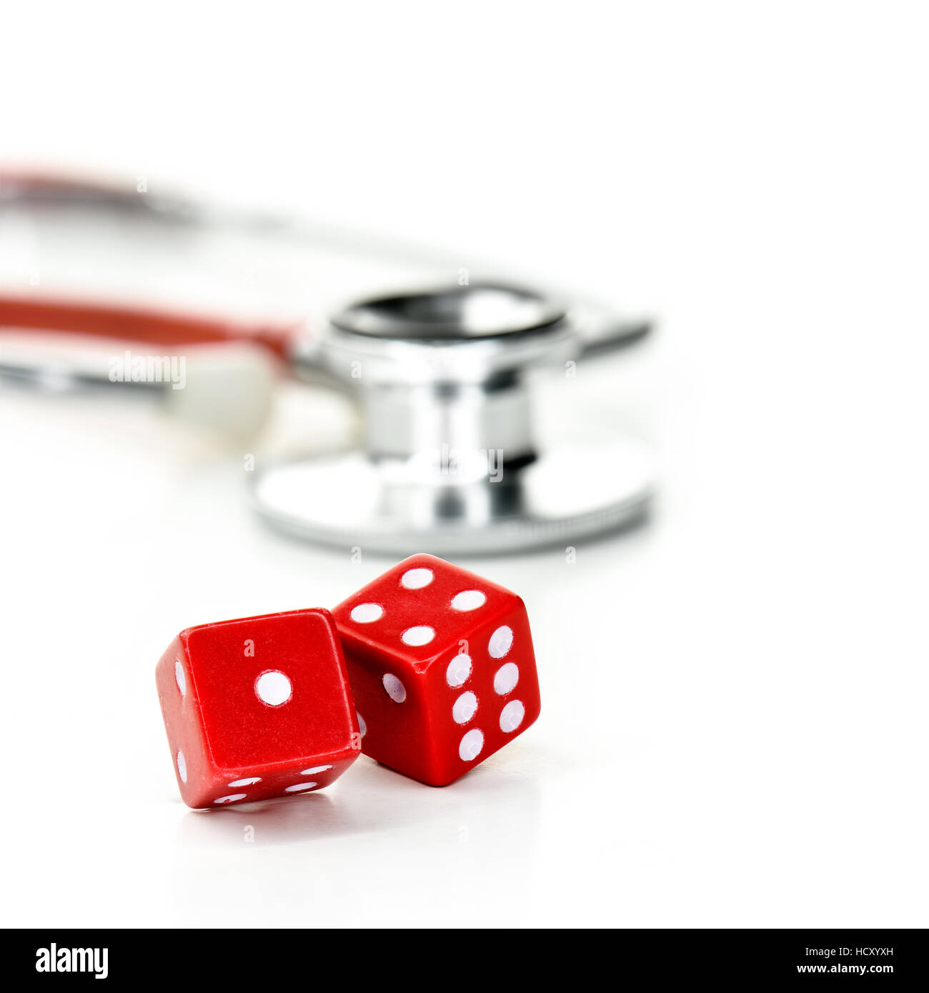 Two red dice and stethoscope with copy space. Concept image for postcode lottery health care, receiving better heal - Stock Image