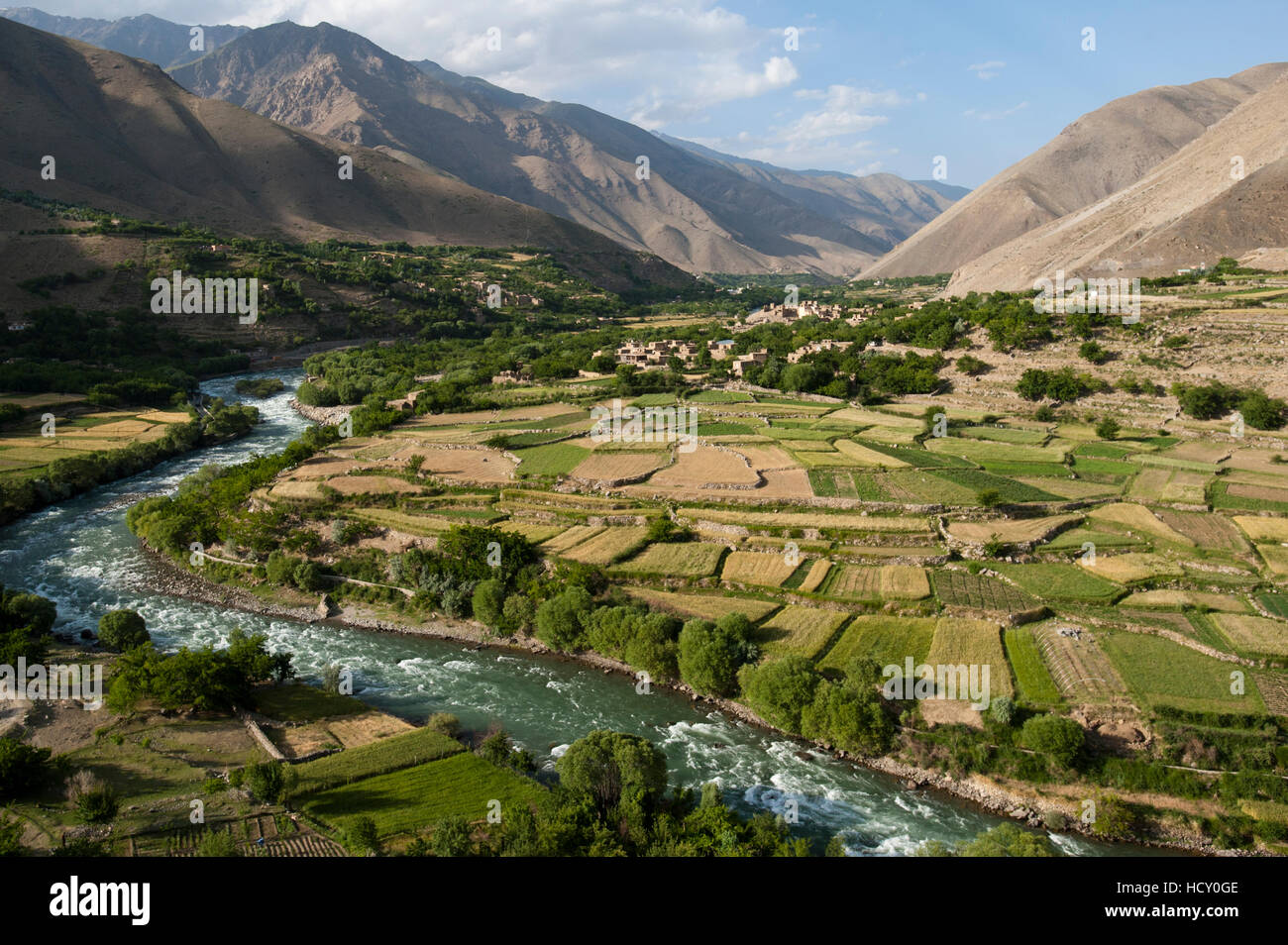 The green of the irrigated fields contrasts with the arid hills above, Afghanistan - Stock Image