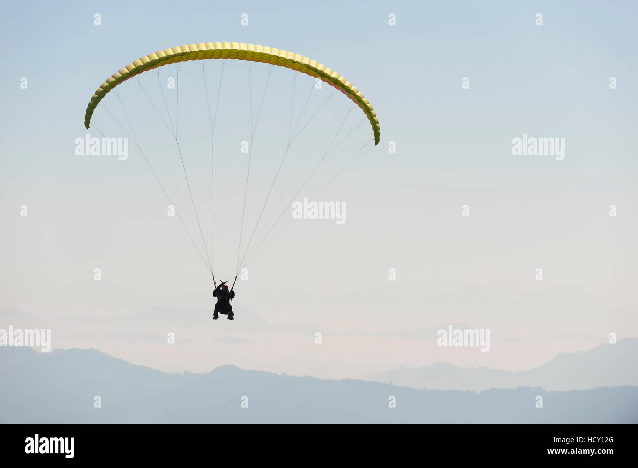 Paraglider flies above Pokhara, Nepal - Stock Image