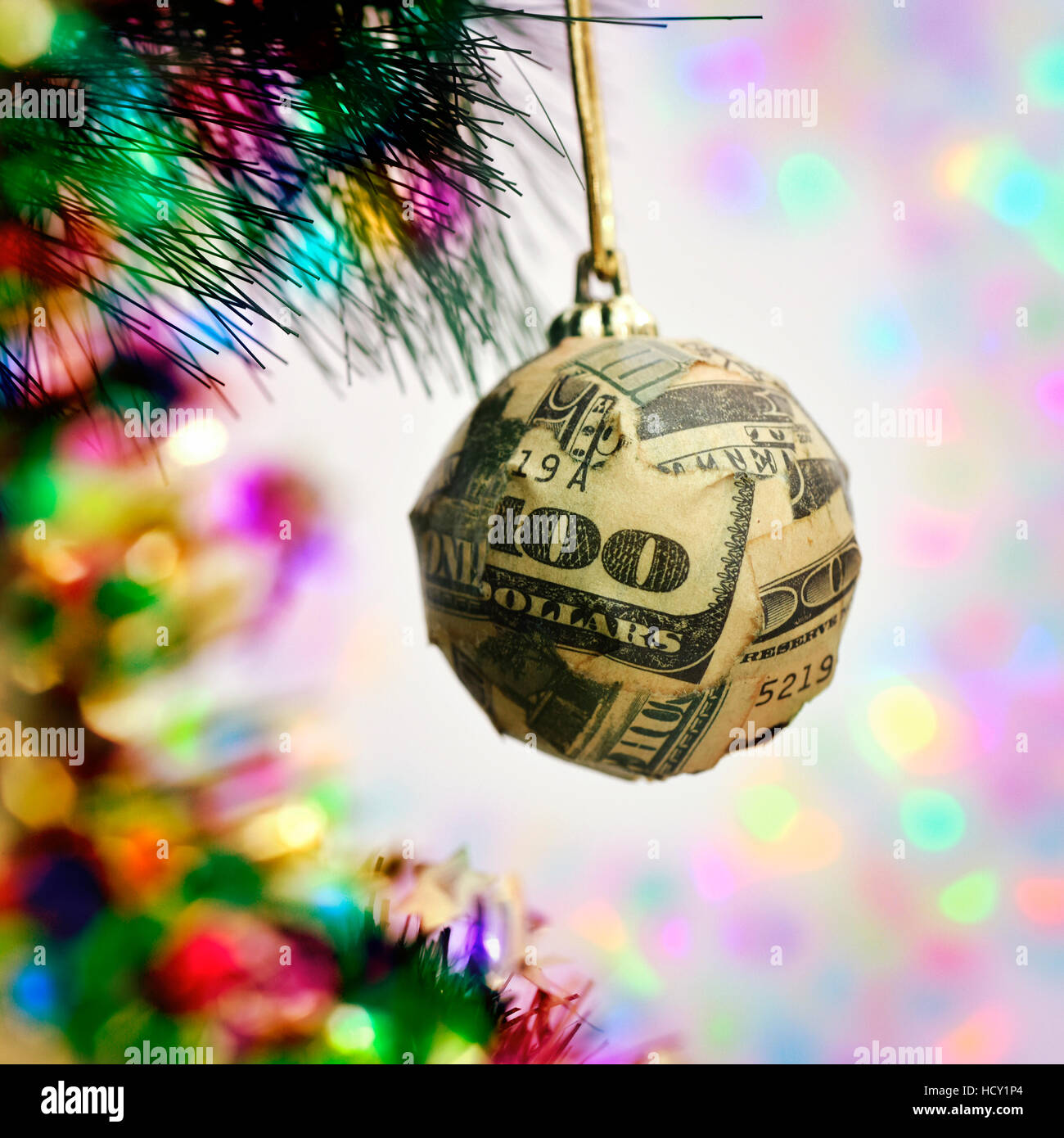 a christmas ball wrapped in pieces of a one hundred dollar banknote hanging from the branch of a christmas tree - Stock Image
