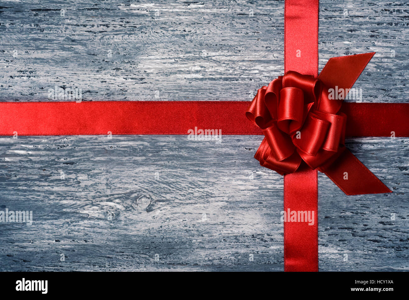 a crossed red satin ribbon tied in a gift bow on a gray rustic wooden surface, with some negative spaces - Stock Image