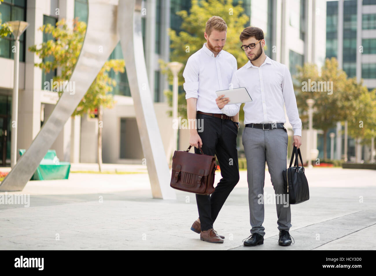 Busy business people using technology on street - Stock Image