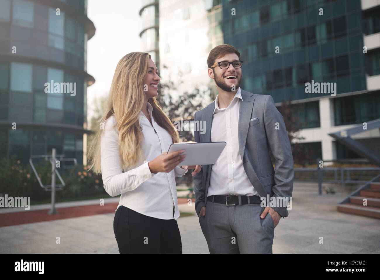Business colleagues talking outdoors and using tablet - Stock Image