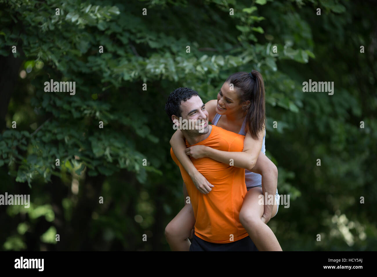 Man carrying woman he loves piggyback - Stock Image