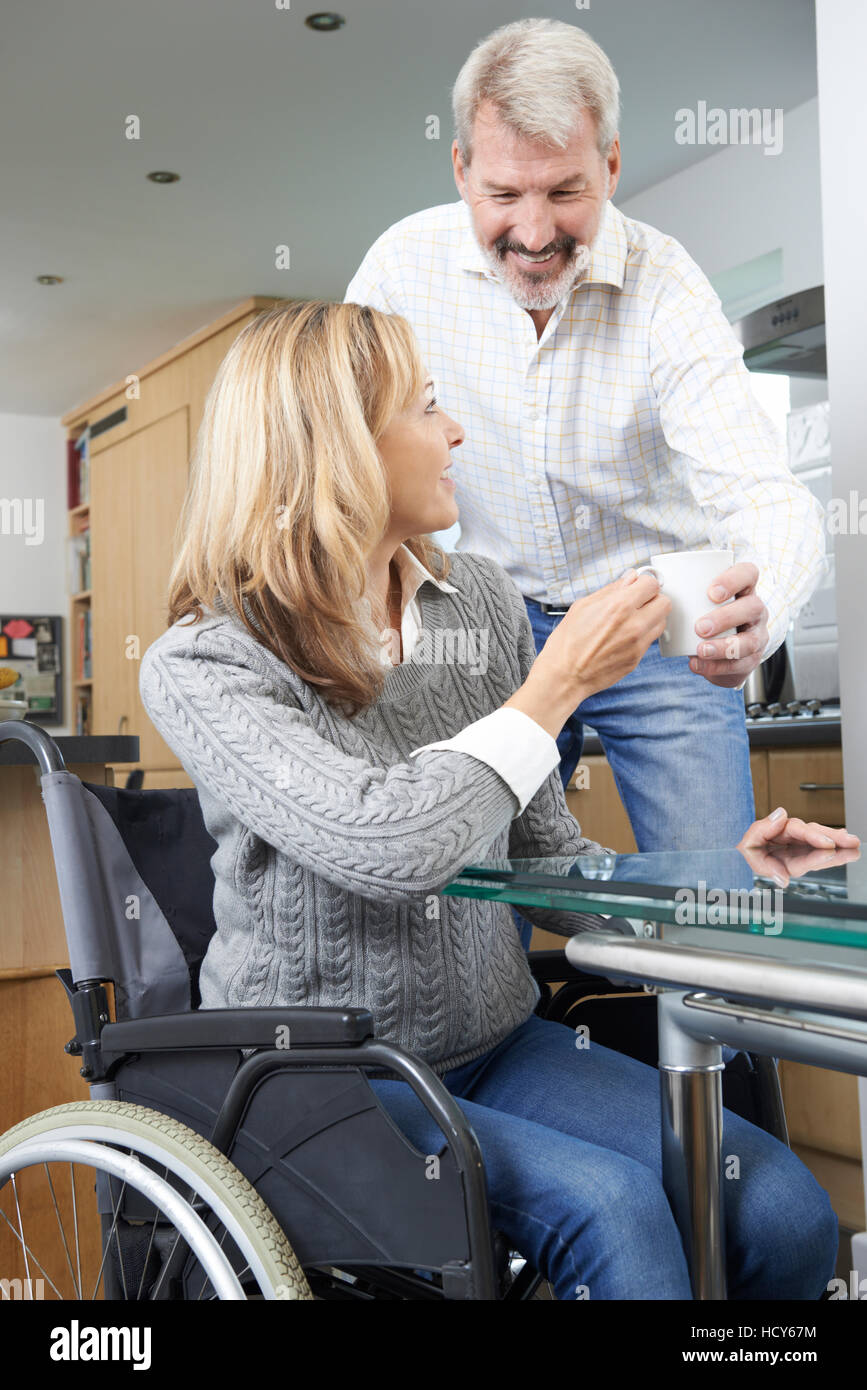 Man Bringing Woman In Wheelchair Hot Drink At Home - Stock Image