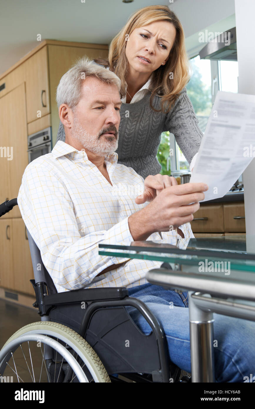Couple With Husband In Wheelchair Reading Letter - Stock Image