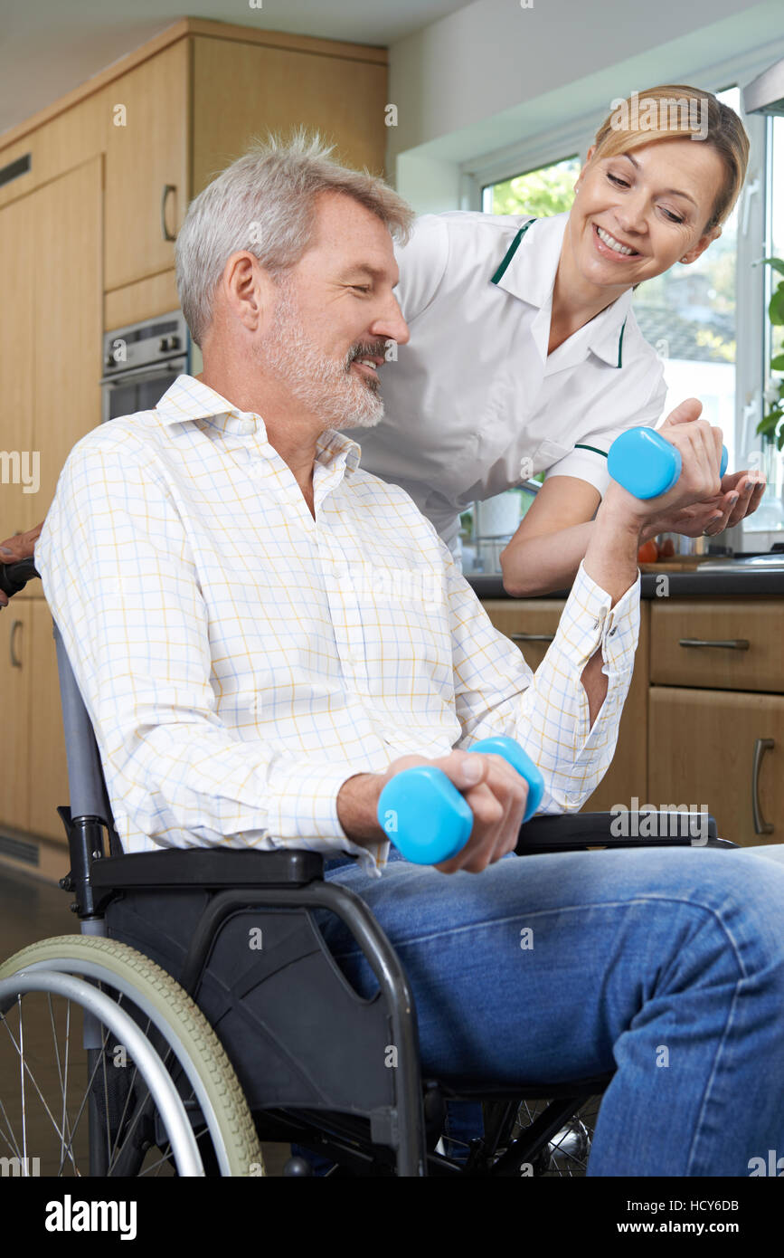 Physiotherapist Helping Man In Wheelchair With Exercises - Stock Image