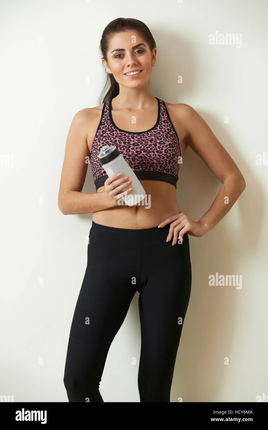 Woman Holding Water Bottle Taking Break During Exercise - Stock Image