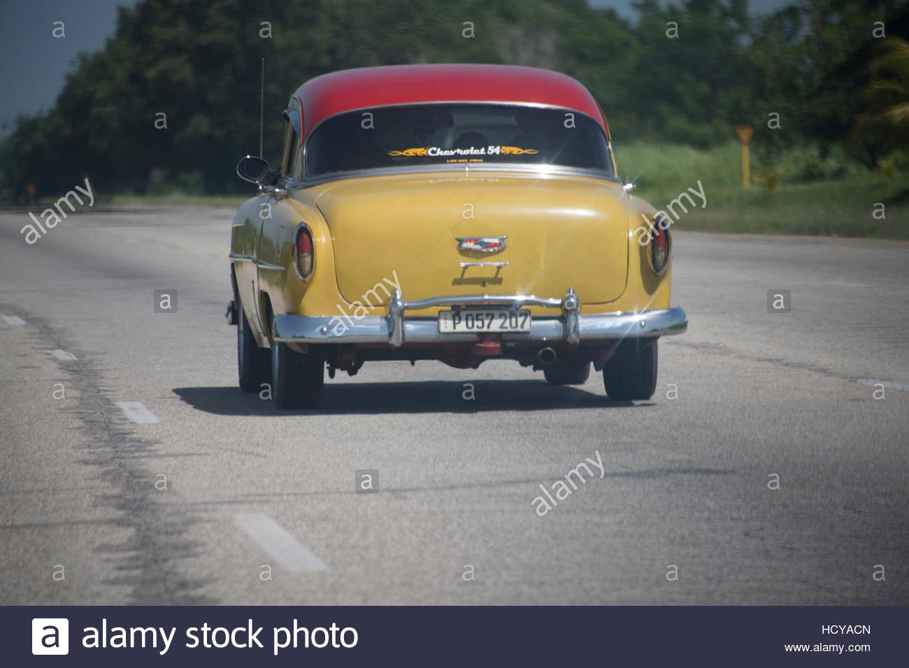Vintage American car Chevrolet driving alone on the highway. There are many trees alongside the road. - Stock Image