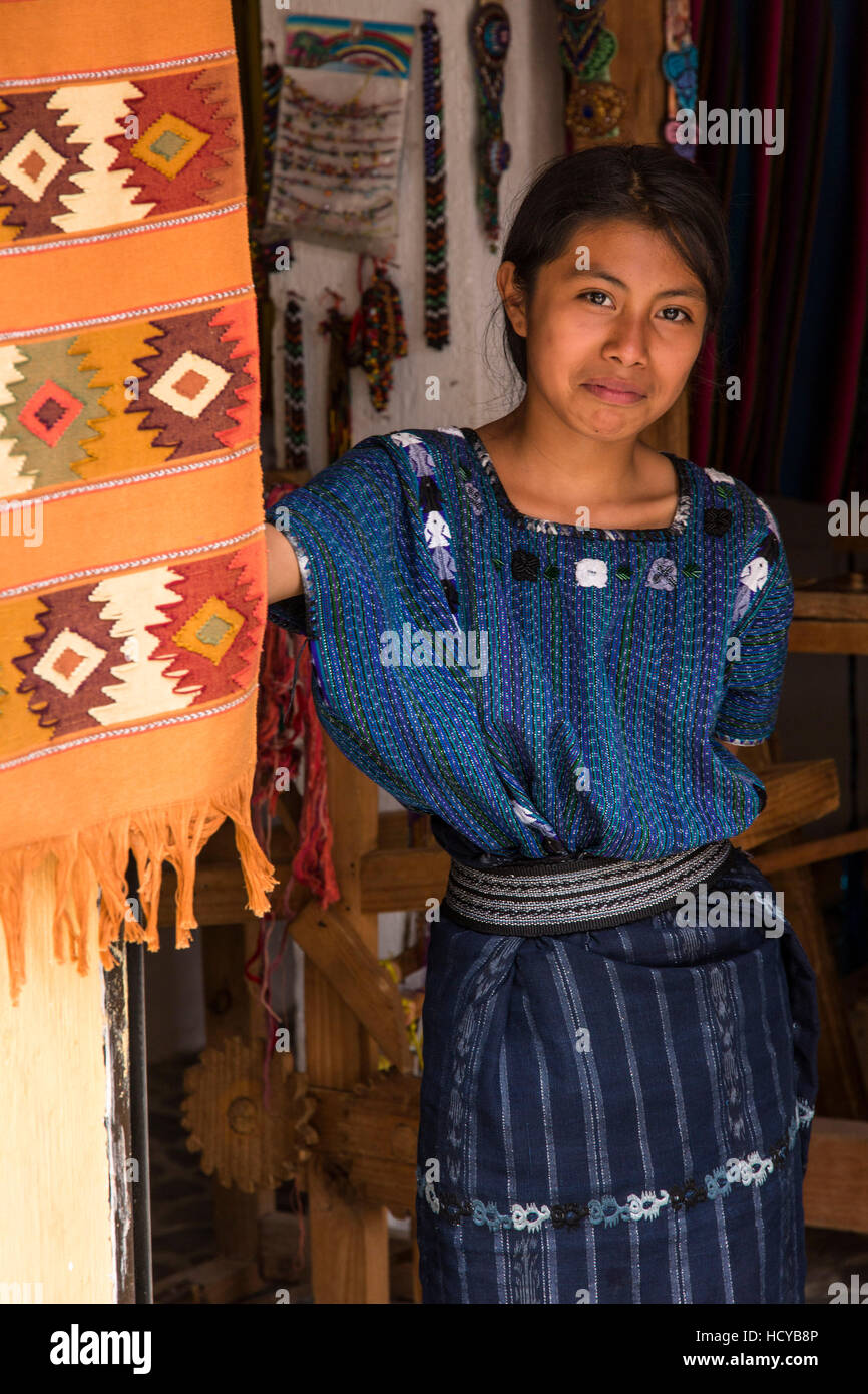 An attractive young Mayan woman wearing typical dress looks out the door of a weaving shop in San Antonio Palopó, Stock Photo