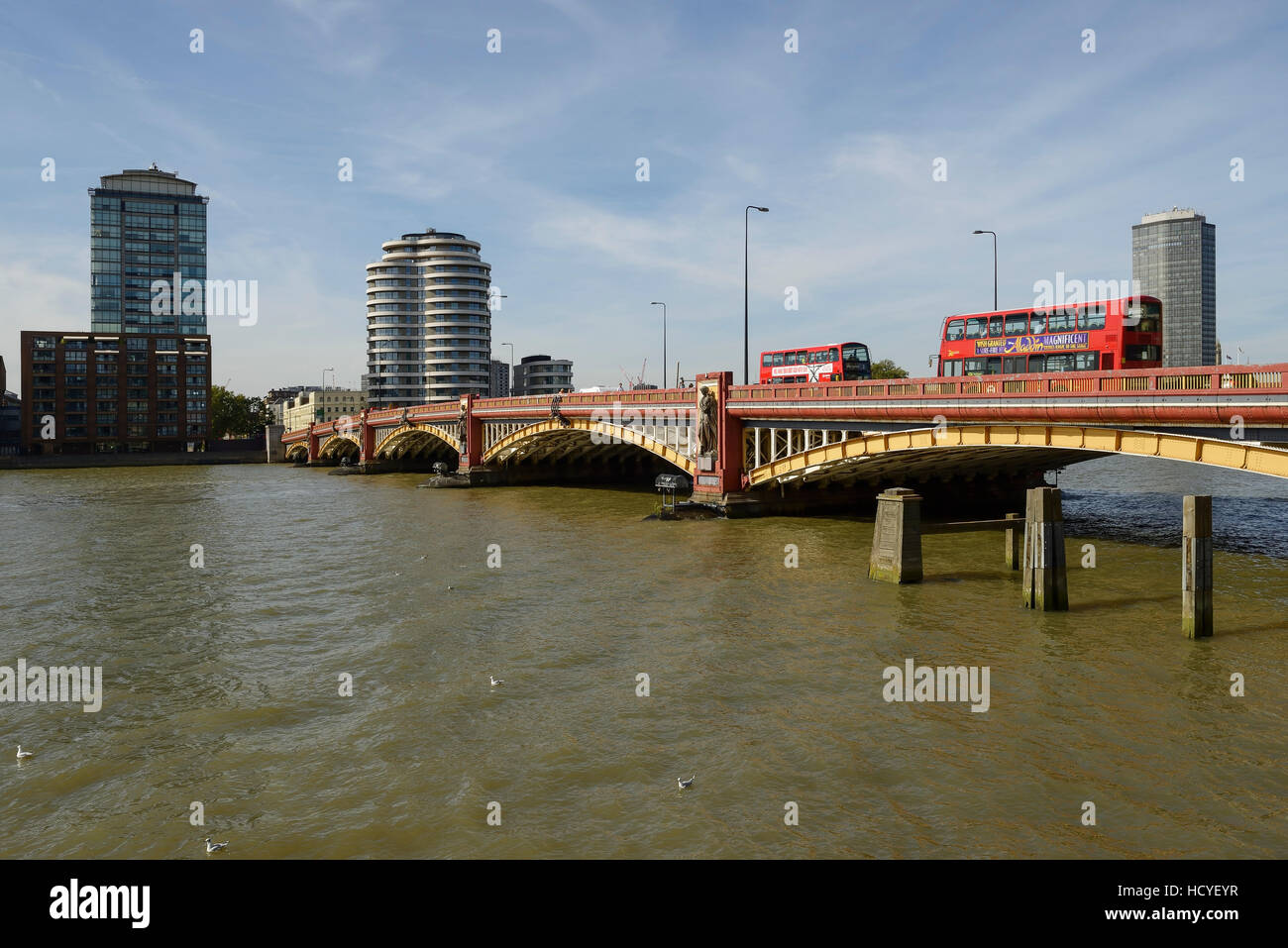 Red london buses cross Vauxhall Bridge in London towards Pimlico - Stock Image