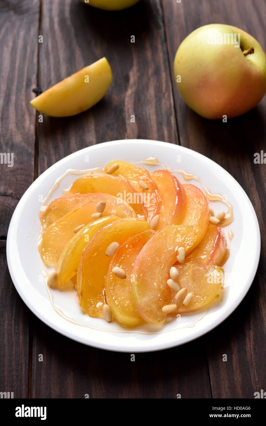 Sweet caramelized apple slices on white plate - Stock Image