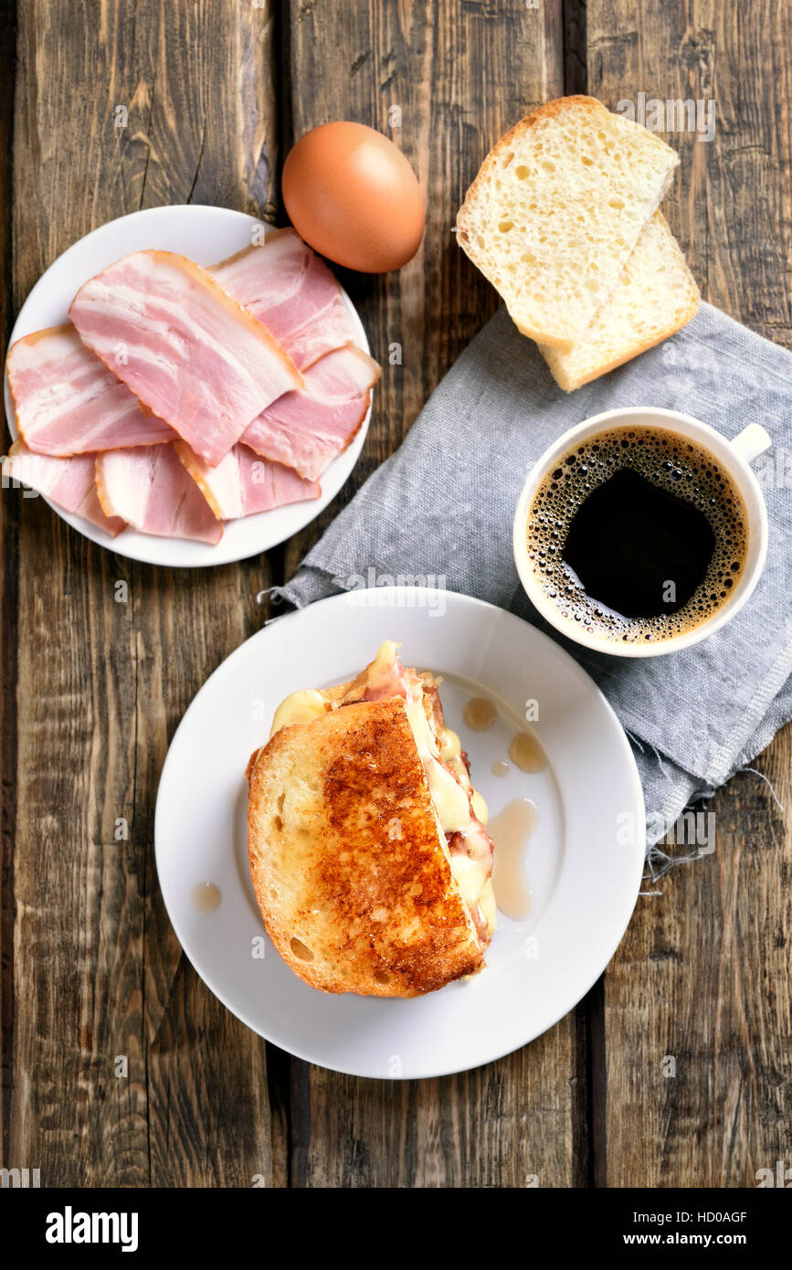 Breakfast toast sandwich with cheese, ham and coffee on wooden background, top view Stock Photo