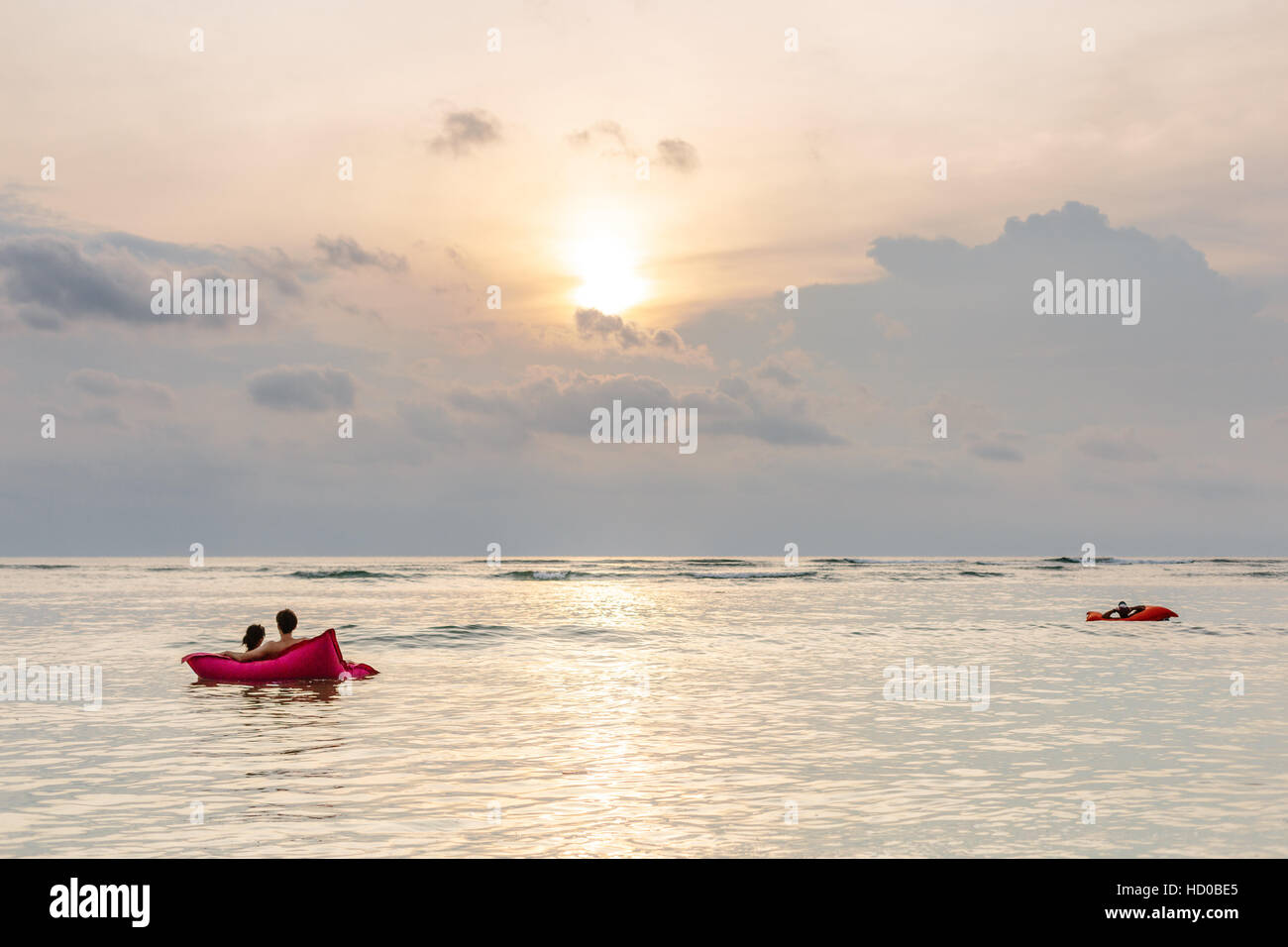 a couple sit on a red floating bean bag in the sea watching the sunset - Stock Image
