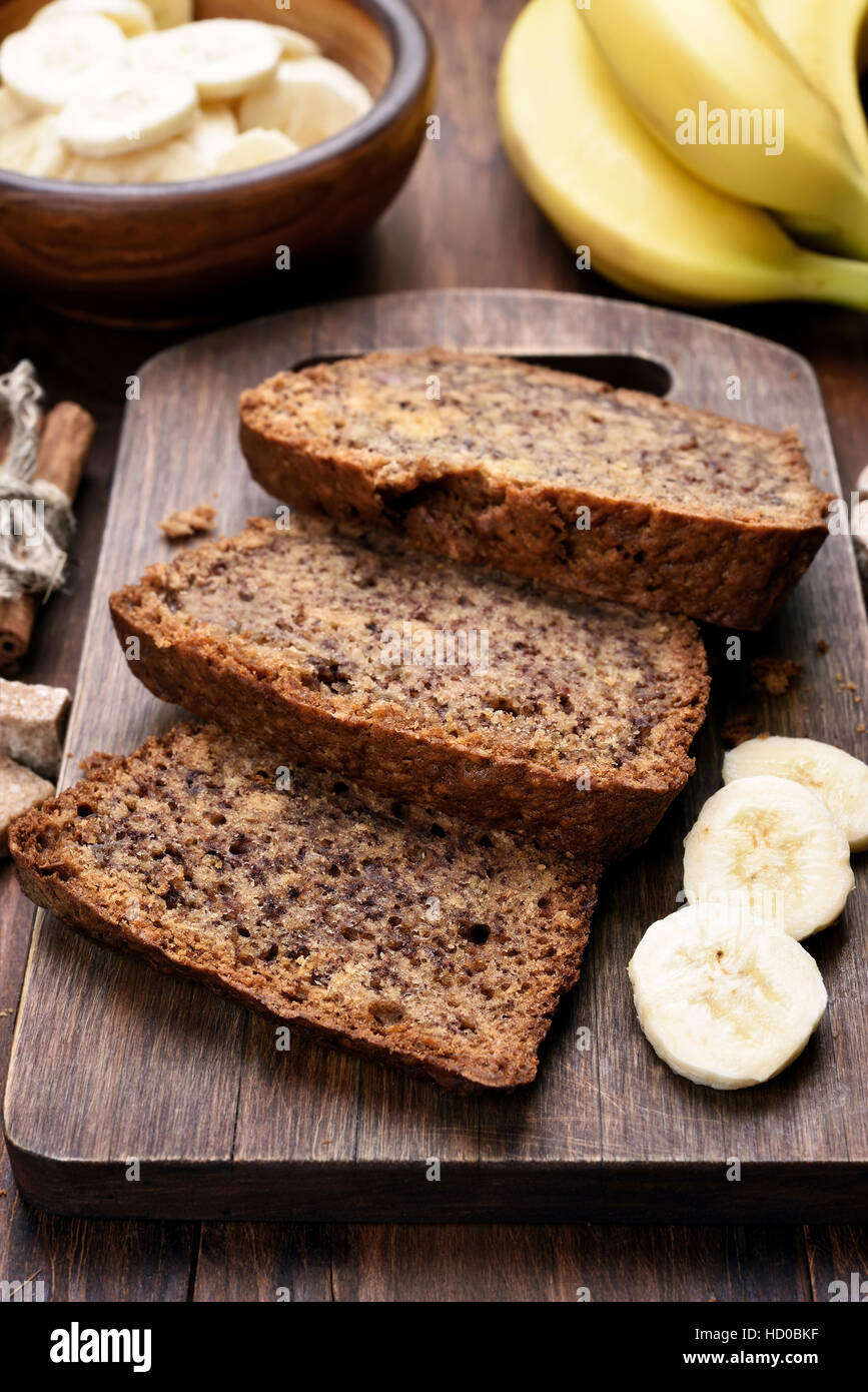Pieces of banana bread on wooden board - Stock Image
