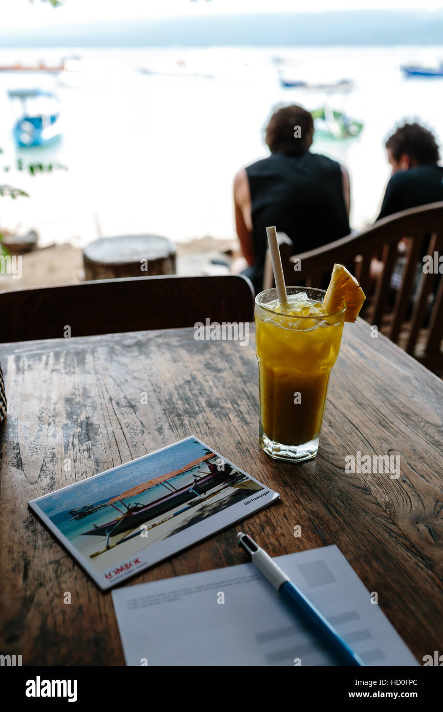 Postcard writing at beachside restaurant on Gili Trawangan, a glass of fresh juice in the foreground. - Stock Image