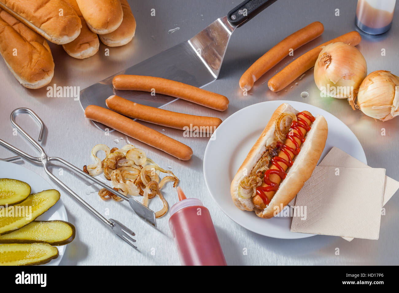 Preparing hot dogs in the stainless steel kitchen of a food truck or hot dog stand. - Stock Image