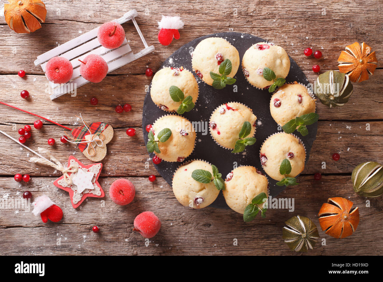 Christmas cranberry muffins decorated with mint close up on the table. horizontal view from above - Stock Image