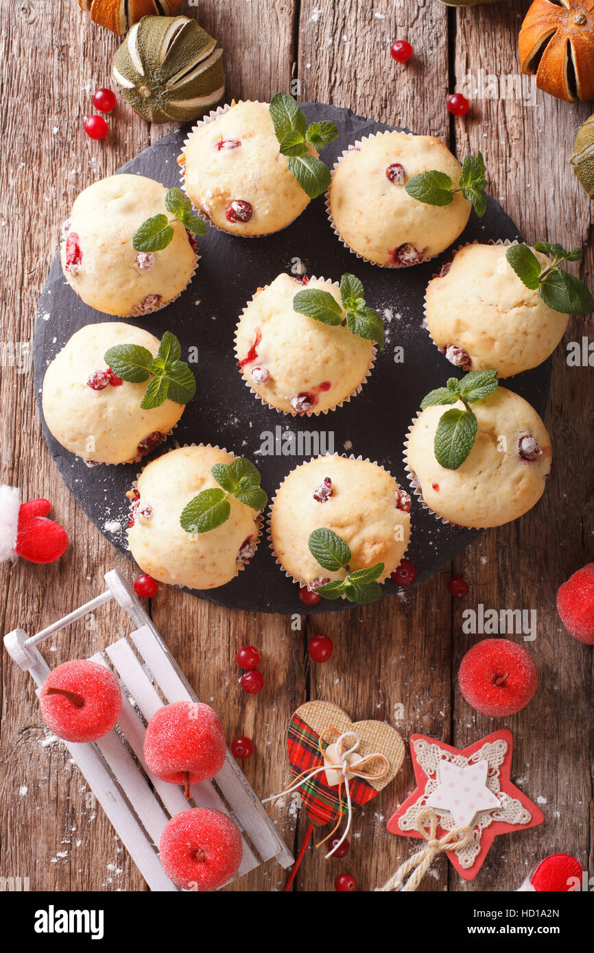cranberry muffins with mint and Christmas decoration close-up on the table. vertical view from above - Stock Image