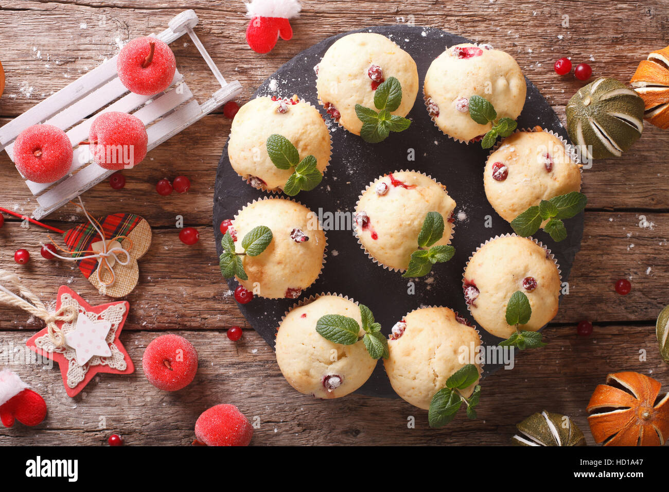 cranberry muffins with mint and Christmas decoration close-up on the table. horizontal view from above - Stock Image