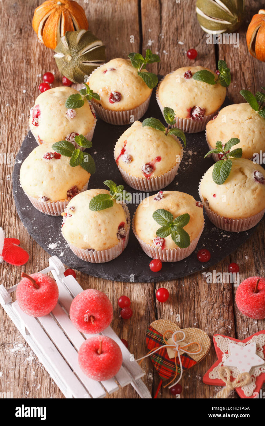 cranberry muffins with mint and Christmas decoration close-up on the table. vertical - Stock Image