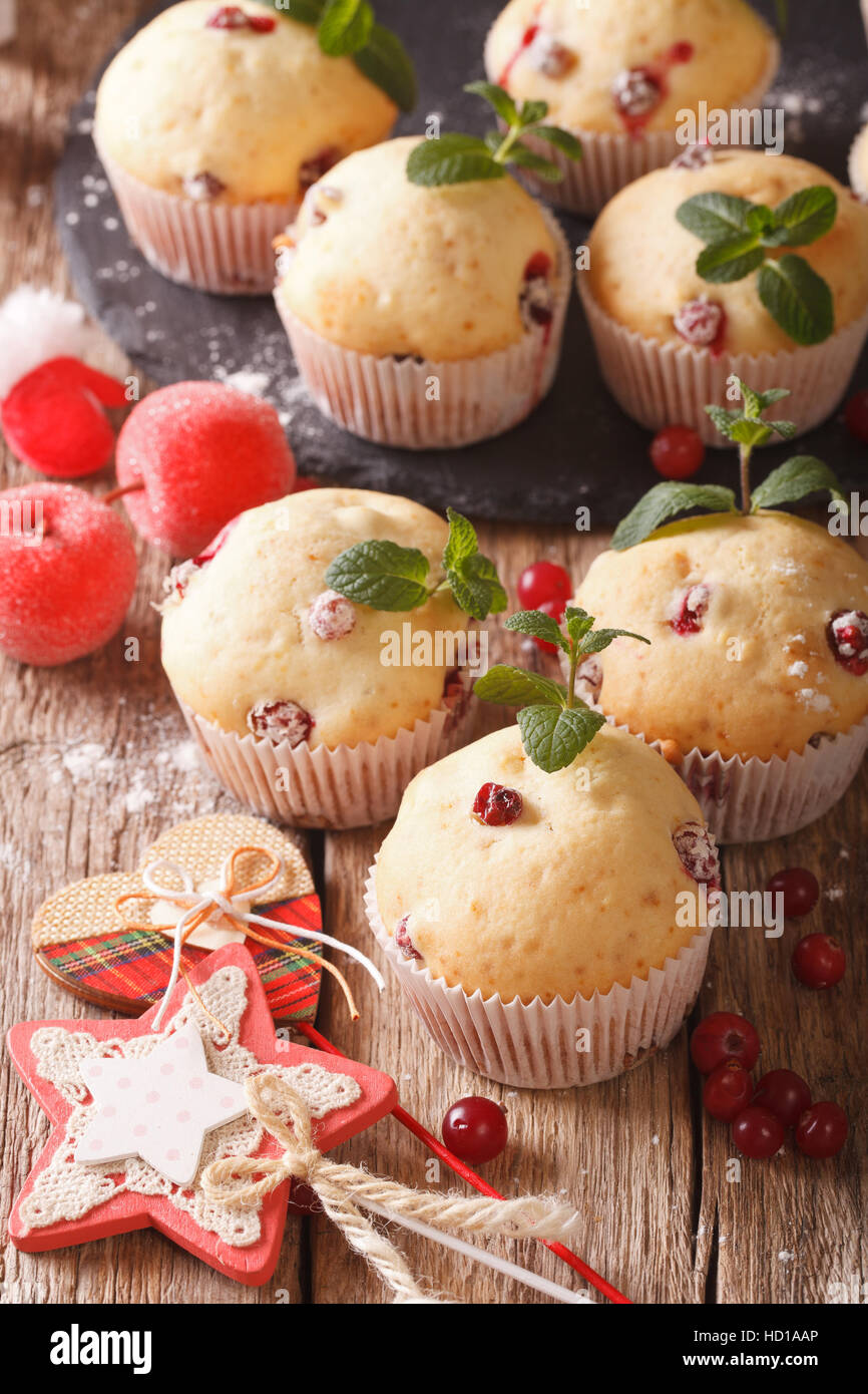 Freshly baked muffins with cranberries close-up on the table. Vertical - Stock Image