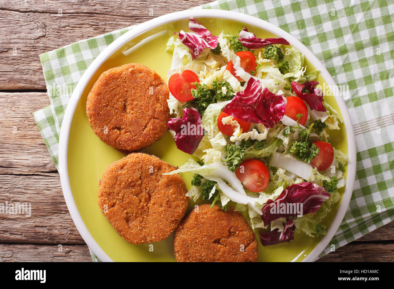 Dietary carrot burgers and fresh salad mix close-up on a plate. Horizontal view from above - Stock Image