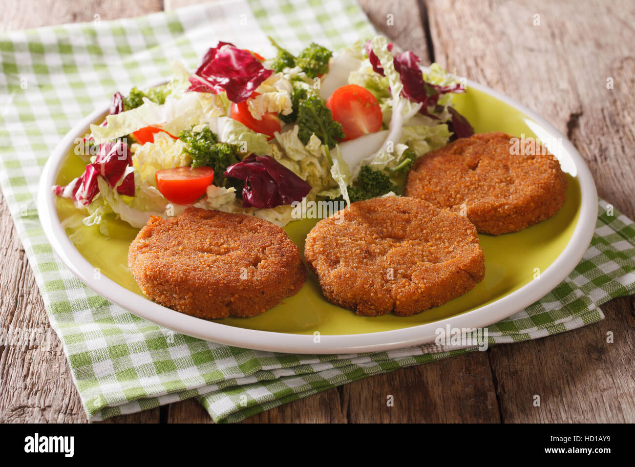 Dietary breakfast: carrot cutlets and salad of chicory, cabbage and tomatoes close-up on a plate. horizontal - Stock Image