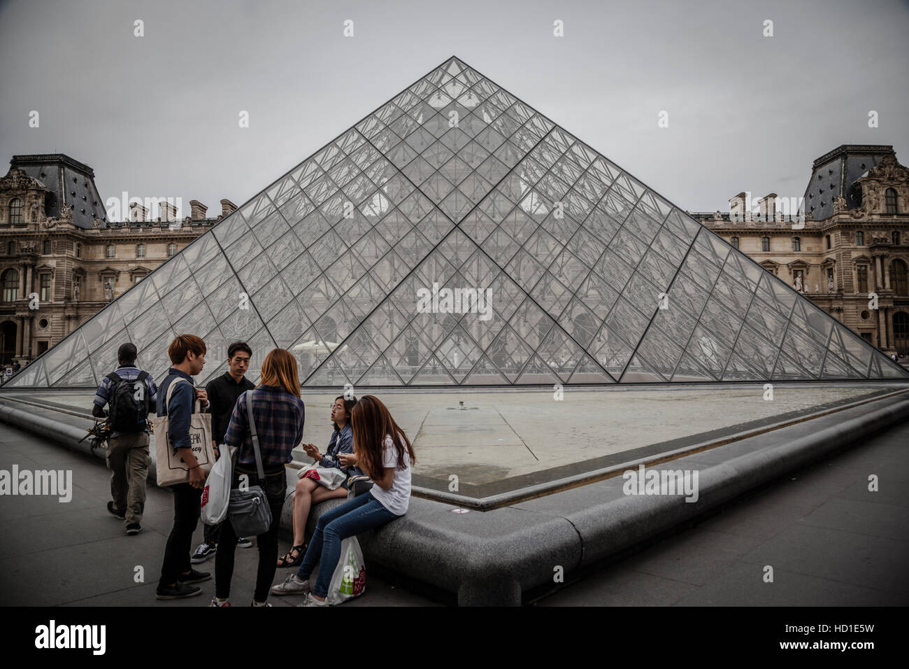 Tourists in the Louvre's central courtyards with the Louvre pyramid and palace. The Louvre is one of the world's - Stock Image