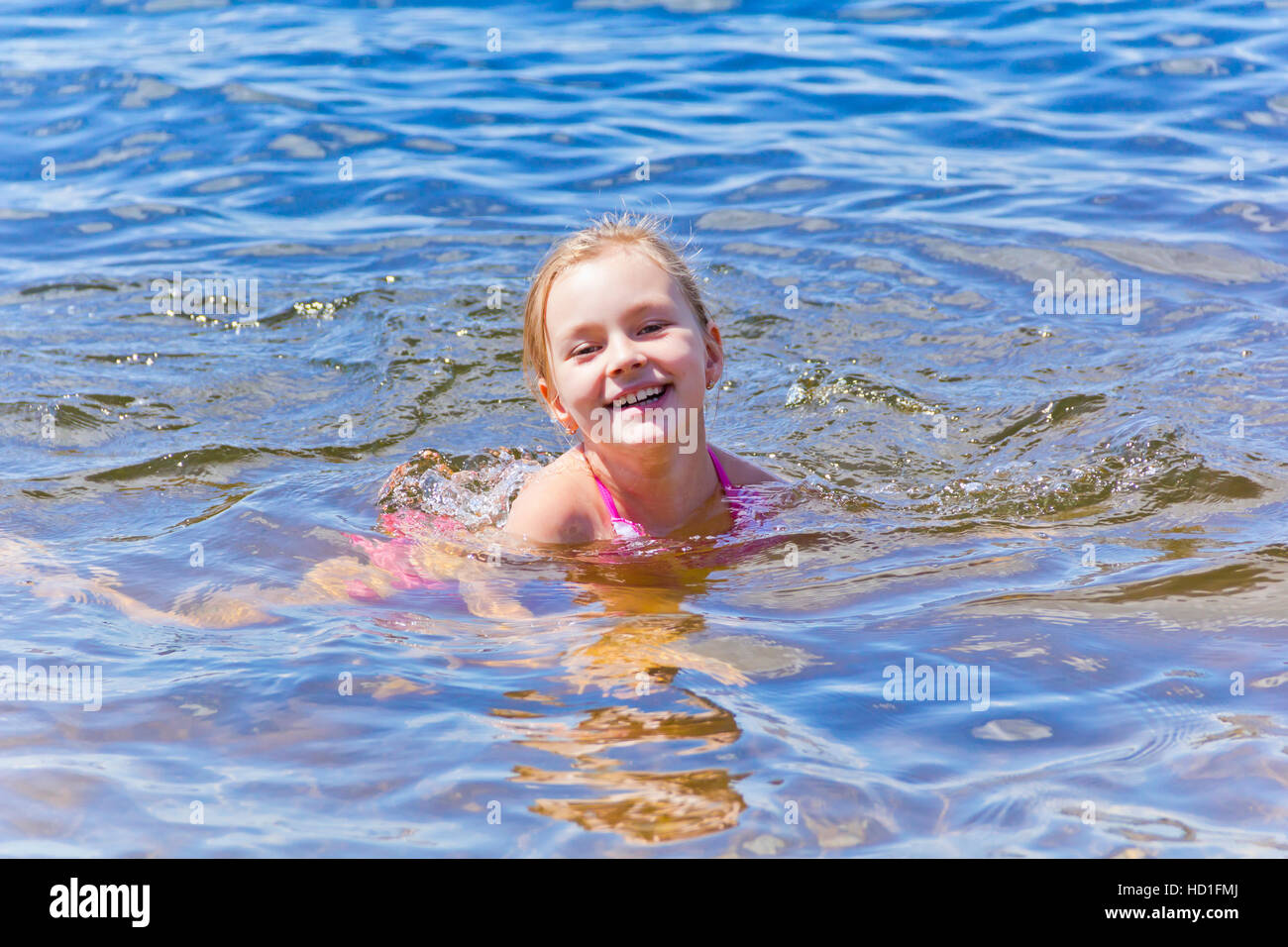 Swimming smiling cute girl seven years old - Stock Image
