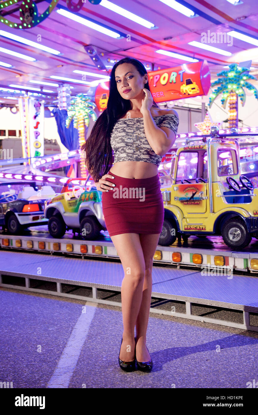 Pretty young woman with long hair in mini-skirt and top at a fun fair. - Stock Image
