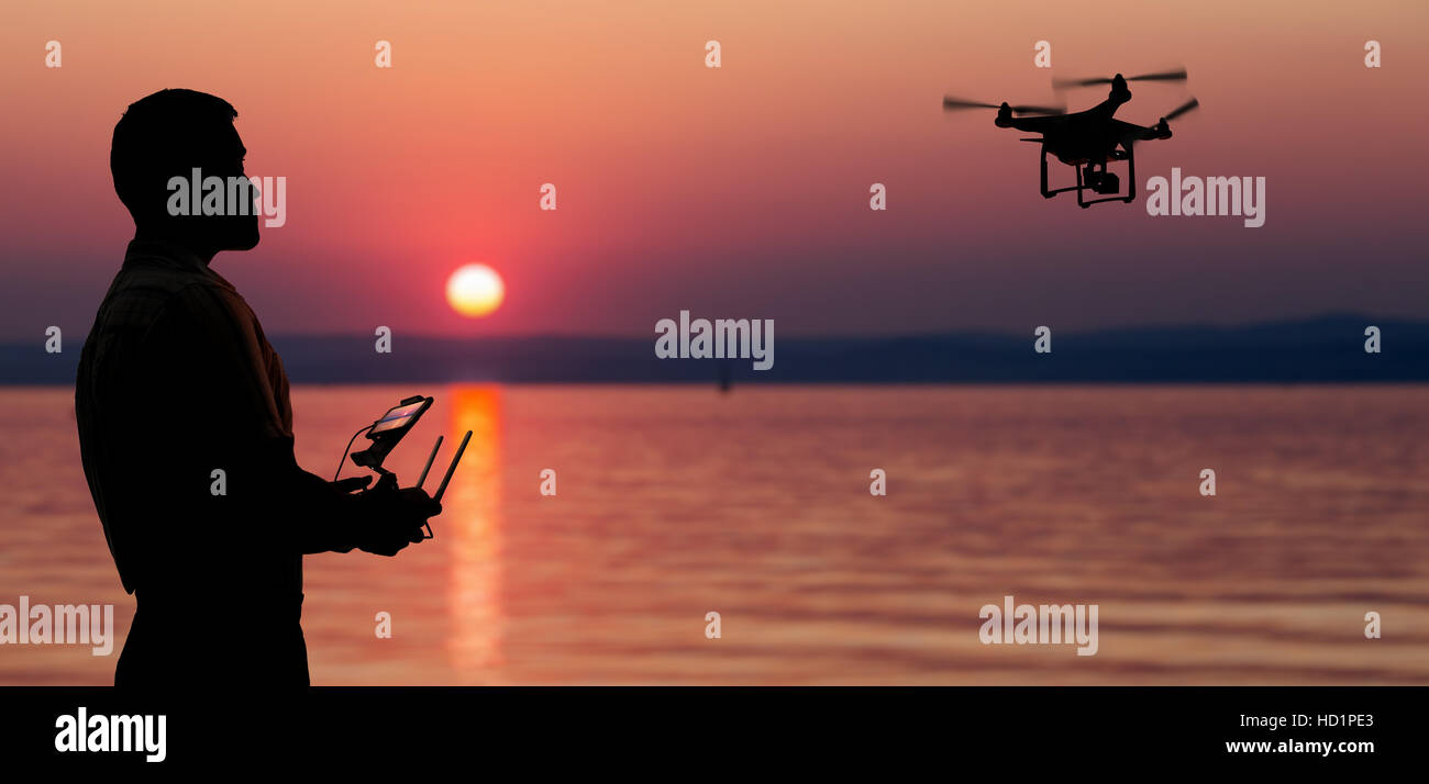 Man flying a drone near seaside at the sunset. - Stock Image