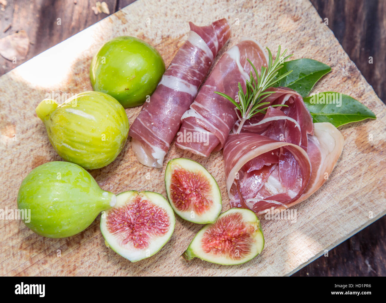Ripe fig fruits and bacon or prosciutto. Food to accompany the drinks. - Stock Image