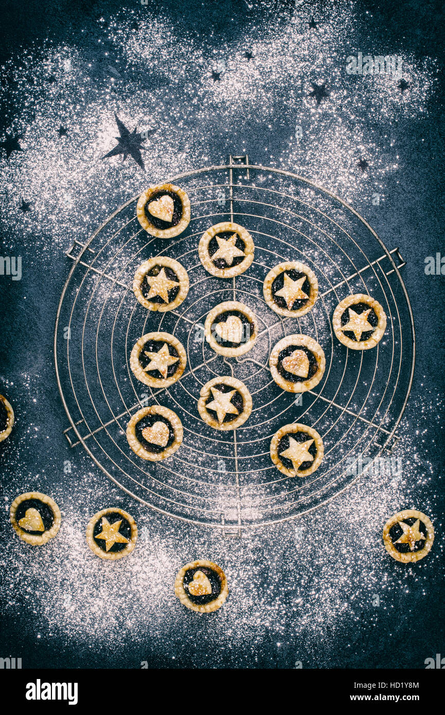 Baked homemade mini mince pies in the shape of a christmas tree with hearts and stars - Stock Image