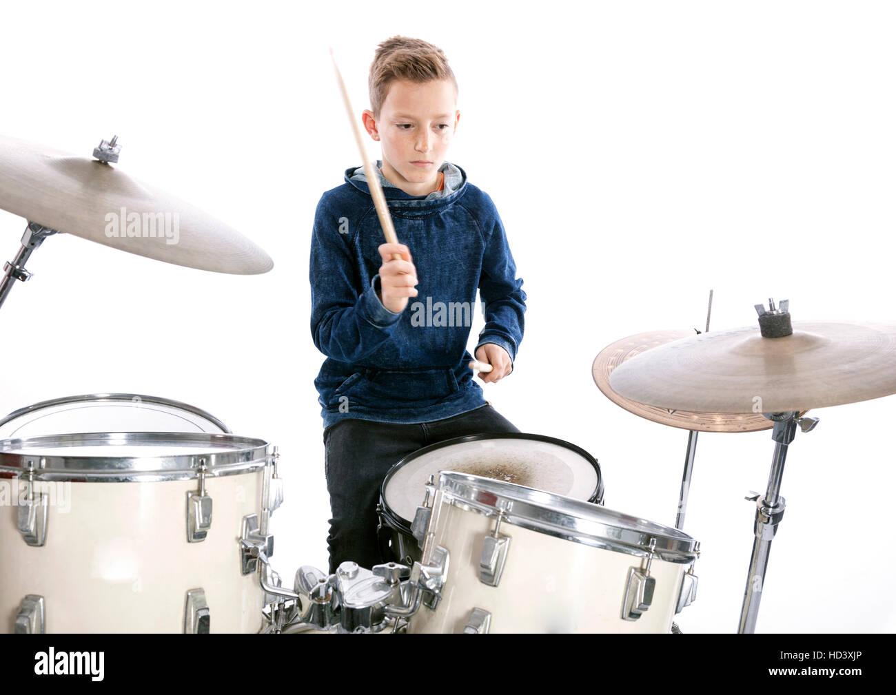 teenage boy behind drum kit in studio against white background - Stock Image
