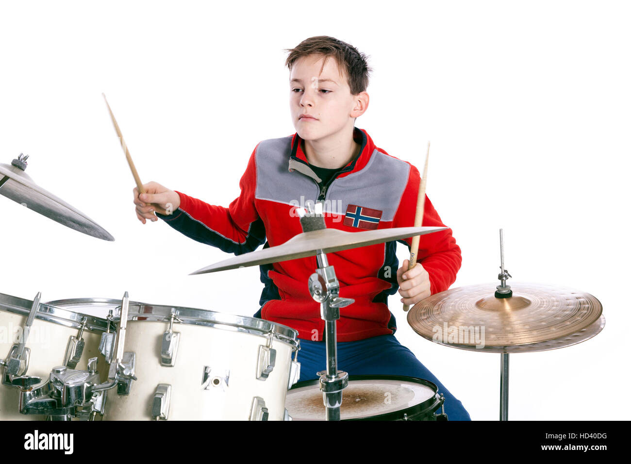 teenage caucasian boy plays drums in studio with white background - Stock Image