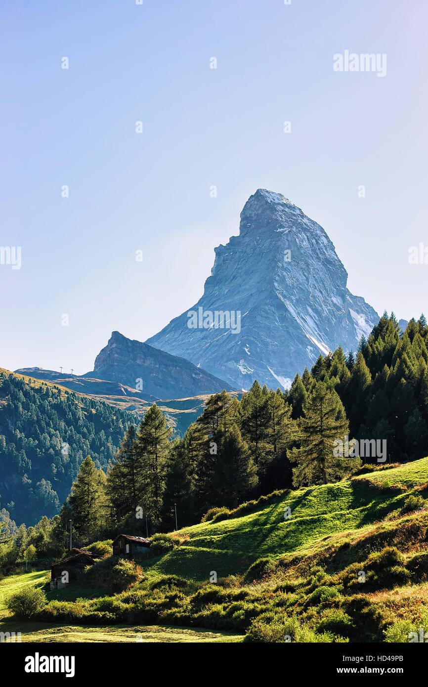 Matterhorn mountain and green valley with chalets in Zermatt, Switzerland in summer. Stock Photo