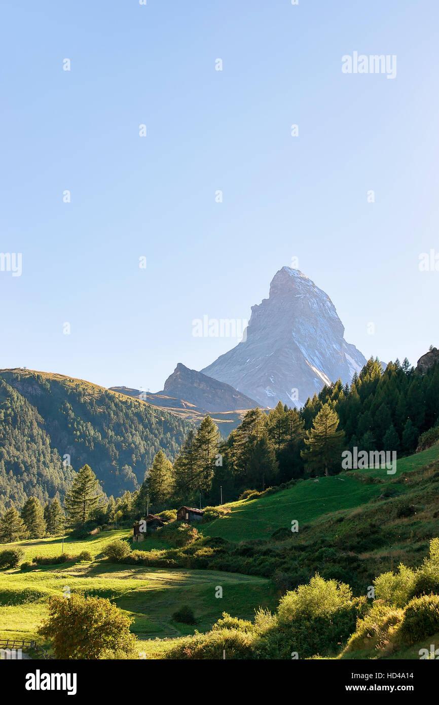 Matterhorn mountain and green valley with traditional Swiss chalet in Zermatt in Switzerland in summer. - Stock Image