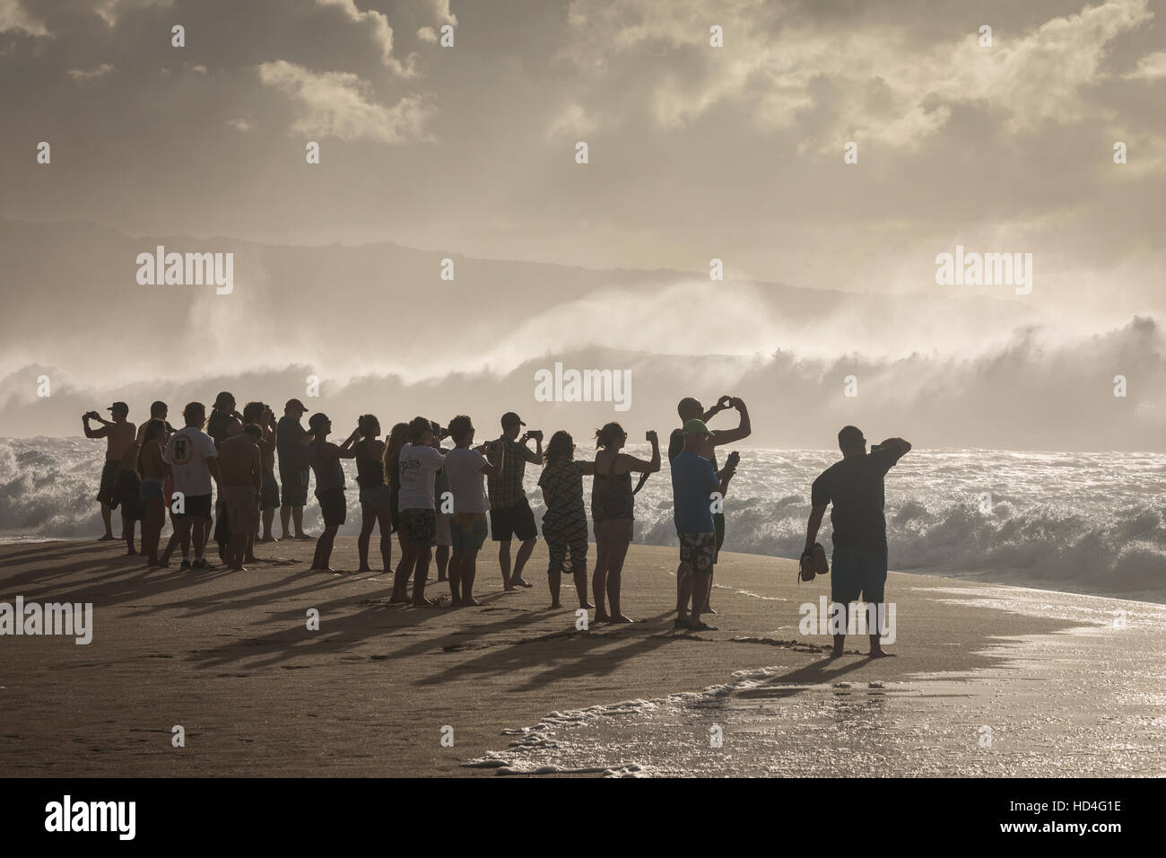 People photographing with their cell phones during a large swell at Pipeline on the North Shore of Oahu. - Stock Image