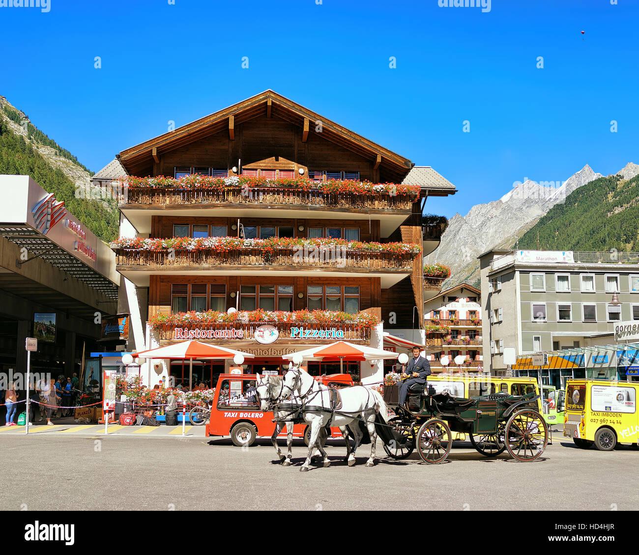 Zermatt, Switzerland - August 24, 2016: Horse vehicle and tourists at City center, Zermatt, Valais canton in Switzerland Stock Photo