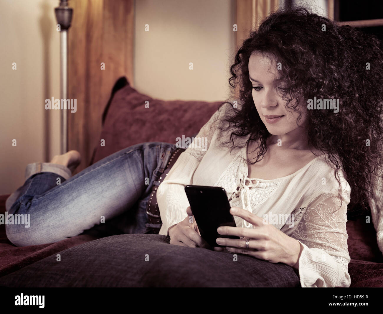 Young woman lying on a sofa at home with Apple iPhone 7 Plus in her hands, reading an e-book - Stock Image