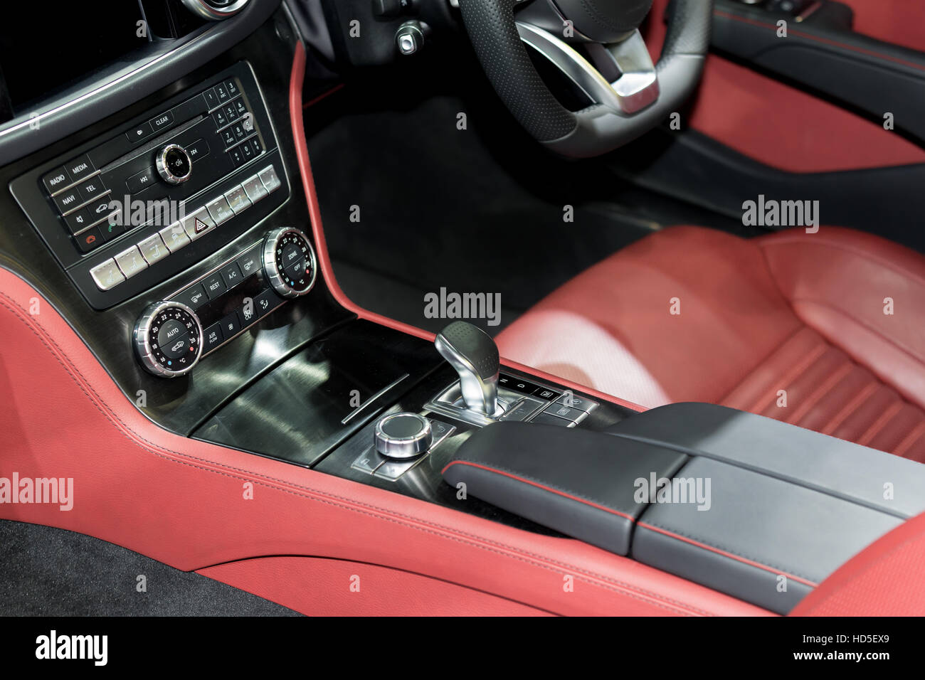 Red luxury car Interior with steering wheel, shift lever and air condition and radio button control in car - Stock Image