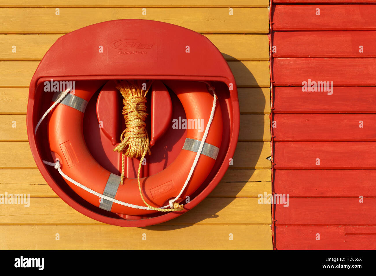 Red lifebuoy hanging on colorful wooden wall, Meschers-sur-Gironde, Charente-Maritime, Poitou-Charentes, France - Stock Image