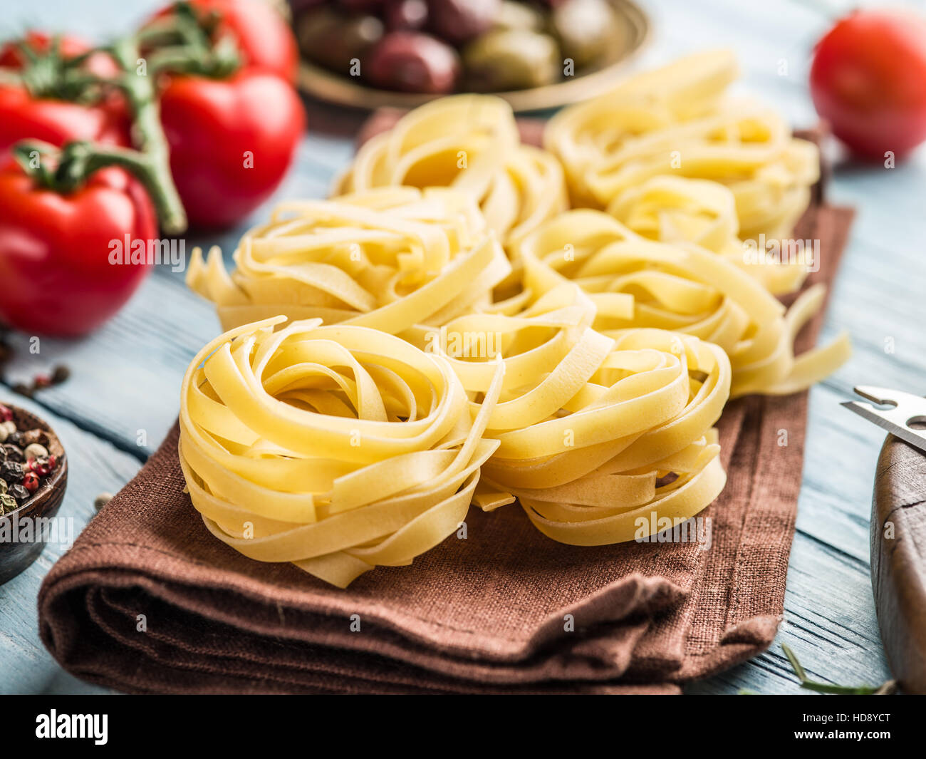 Pasta ingredients. Cherry-tomatoes, spaghetti pasta and spices on the wooden table. - Stock Image