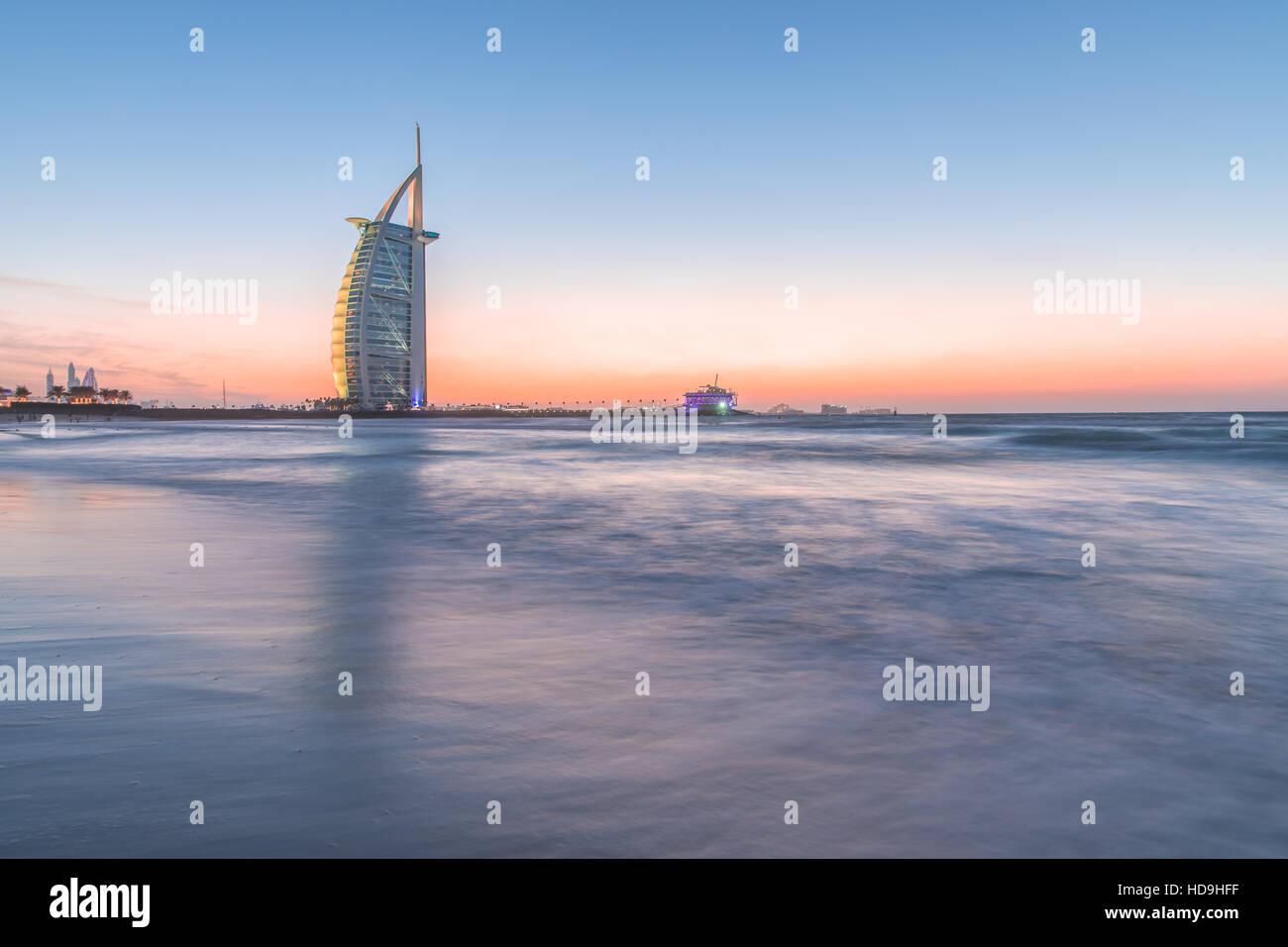 Luxury hotel Burj Al Arab on the coast of Persian Gulf after sunset. Dubai, UAE. - Stock Image
