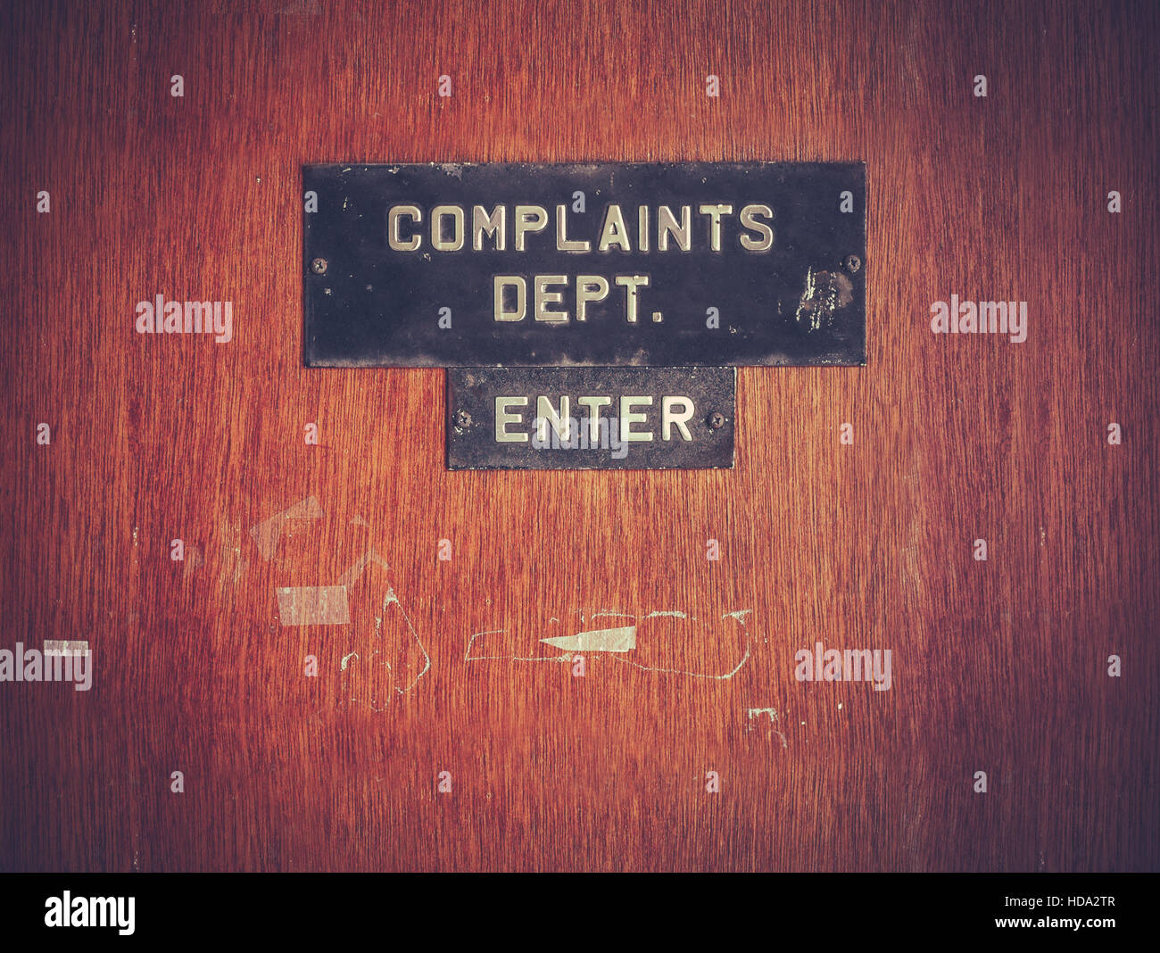 A Grungy Complaints Department Sign On A Door - Stock Image