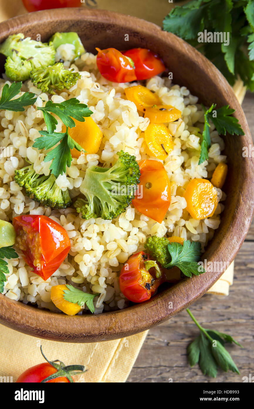 Delicious homemade vegetarian bulgur (couscous) with vegetables: tomatoes, carrots, zucchini, broccoli and parsley Stock Photo